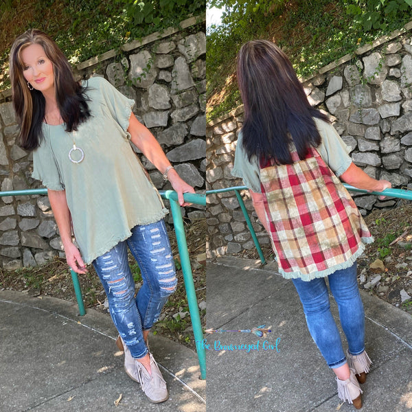 Woman wearing a sage mint frayed hem tunic with plaid accented back.