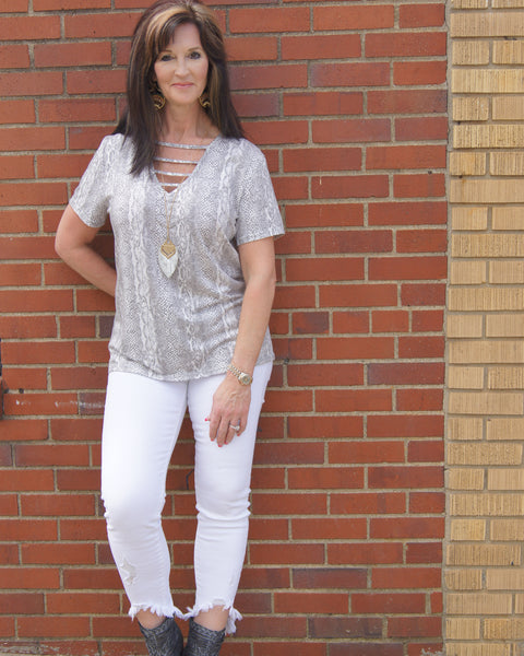 Woman wearing a short sleeve  grey and white snake skin v-neck top. Material is soft and stretchy. Model wearing size large. Thebrowneyedgirl boutique