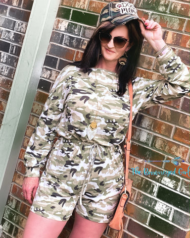 Woman wearing a olive and grey camo long sleeve romper. It's figure flattering with a cinched waist fits true to size. Material is very comfortable can be worn on or off the shoulder. The-Brown-eyed-Girl-Boutique