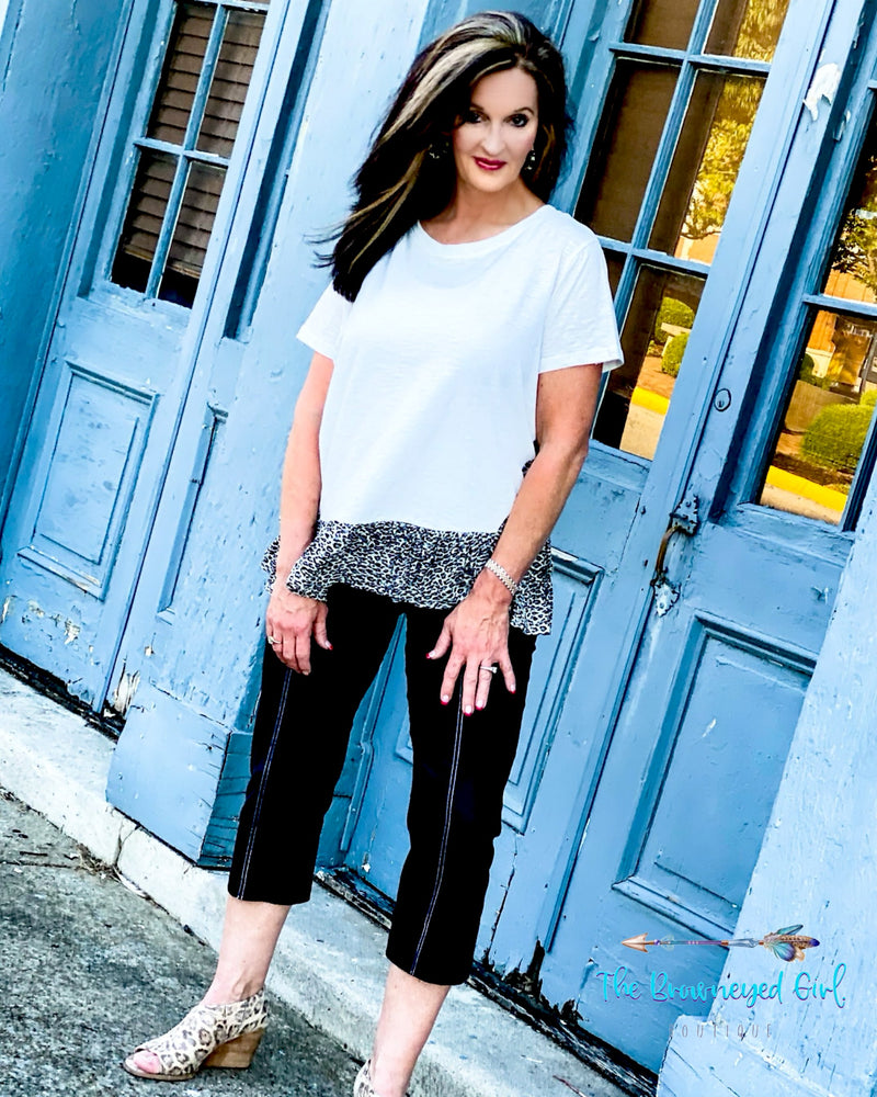 Woman wearing Umgee snow leopard white relaxed fit short sleeve top. Trimmed in a black and white leopard ruffle.