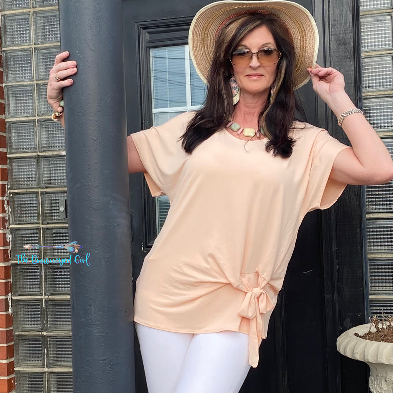 Woman wearing a dressy casual light peach short sleeve top with front tie. This top is super cute soft and light weight