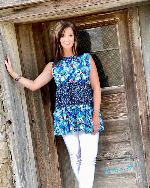 Woman wearing a beautiful blue floral mixed print ruffle layered tunic.  Material is light weight perfect for spring and summer . This top fits true to size  model size 7 wearing medium