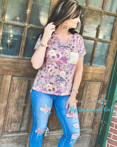 Woman wearing a v-neck mauve floral lace pocket tee. This top is short sleeve ultra comfortable pairs with denim and our Sierra Ribbed Knit Cardigan.