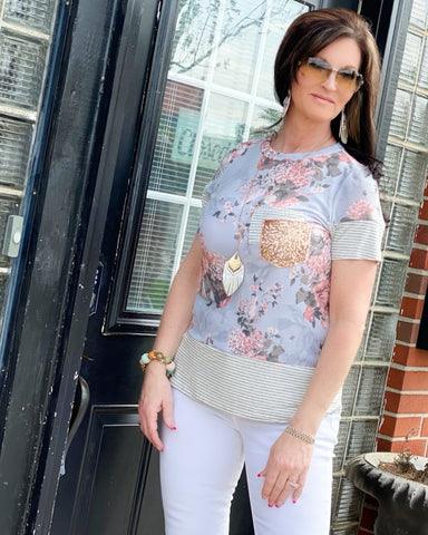 Woman Wearing Light Grey Spring Floral Short Sleeve Top With Double  Front Pockets. Grey And White Stripe,Sequin. Bodice is Fitted Accented With Grey And White Stripe Bottom. USA MADE Fits True To Size