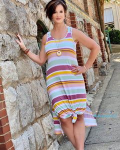 Woman wearing a tank style maxi dress with stripes in soft summer colors. This dress is perfect for summer and pairs with our ribbed knit cardigans. Model is size 7 wearing a medium