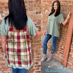 woman wearing a sage mint short sleeve top with frayed hem details. The back is accented with a fall plaid pattern.