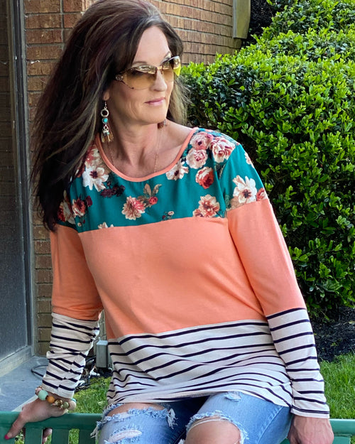 Woman wearing a color block tunic in teal, coral and stripe ,long sleeve .  This Top is Beautiful. Material is ultra soft and stretchy  fits true to size.
