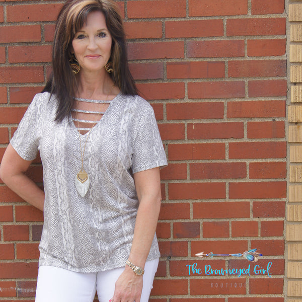 Woman wearing a grey and white snake skin v-neck top with straps across the v. Short sleeve material is soft and stretchy fit true to size.
