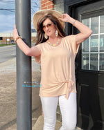 Woman wearing a light peach colored short sleeve top. With a crew neck line and front tie . This top is dressy casual  light weight fits true to size.