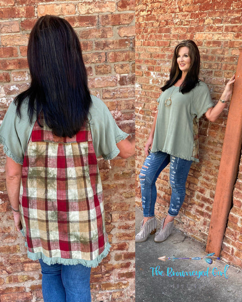 Woman wearing a sage mint frayed hem short sleeve top. The back is accented with fall plaid details.