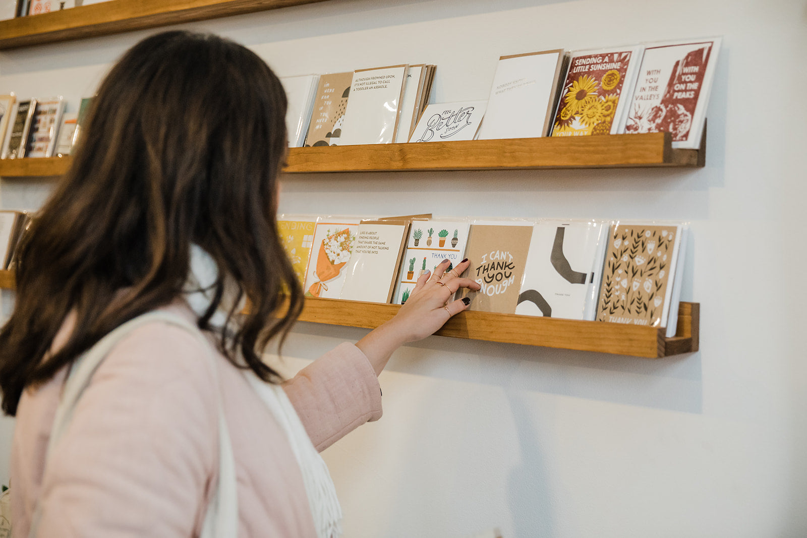 Woman browsing a variety of greeting cards along a wall.