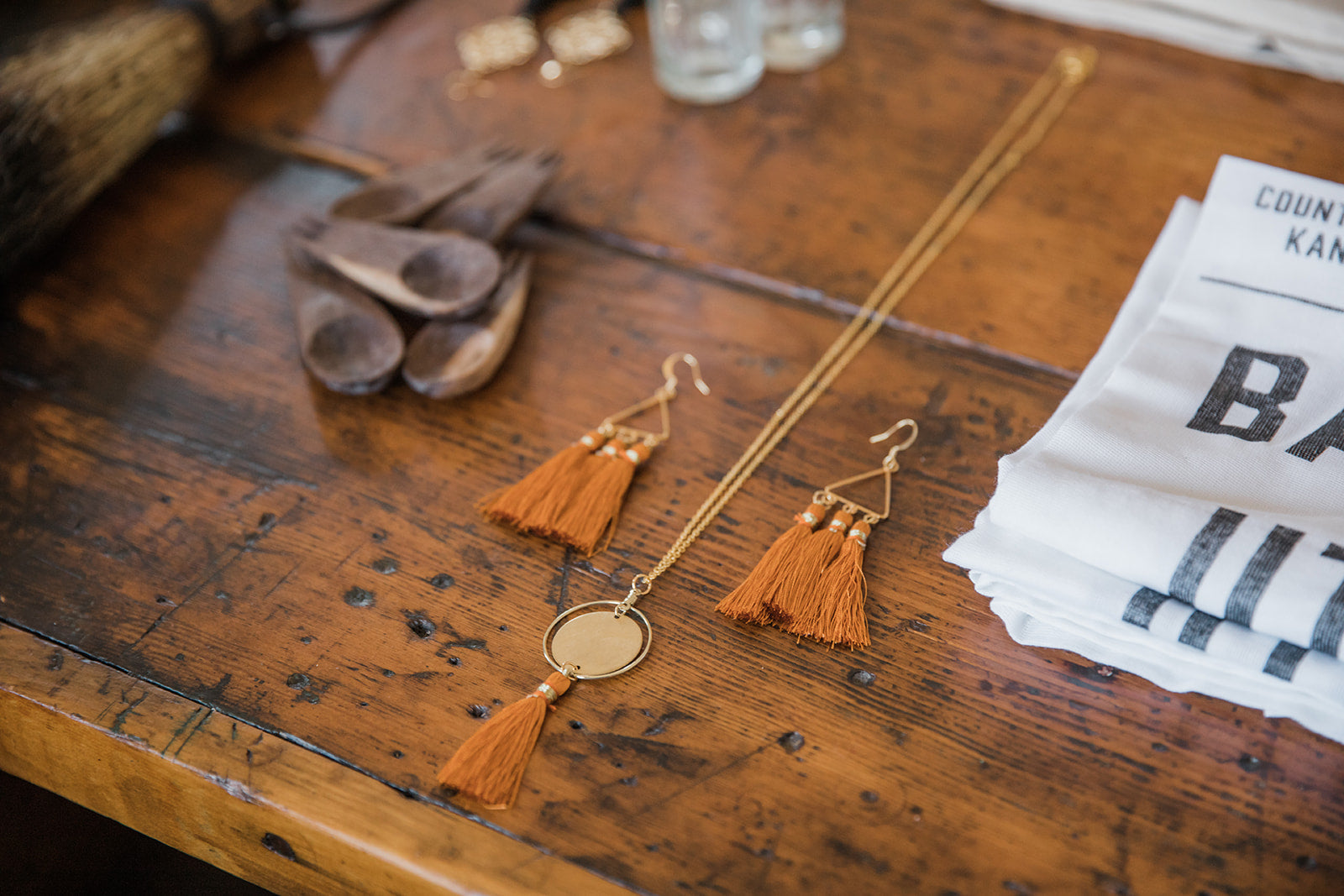 Natalie Claire jewelry on a wooden table.