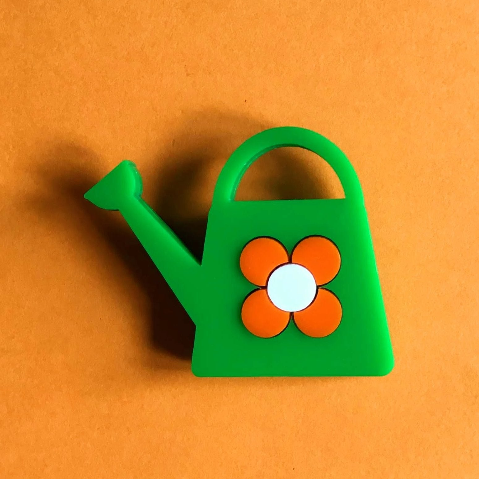 Little green watering can , with an orange flower🌼 - Isa Duval