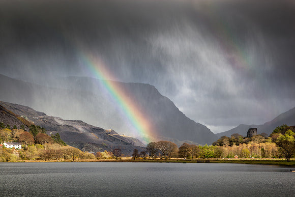 Four Seasons in One Day - Llanberis, Snowdonia - two rainbows can be seen through the storm clouds and rain above the lake of Llyn Padarn in North Wales