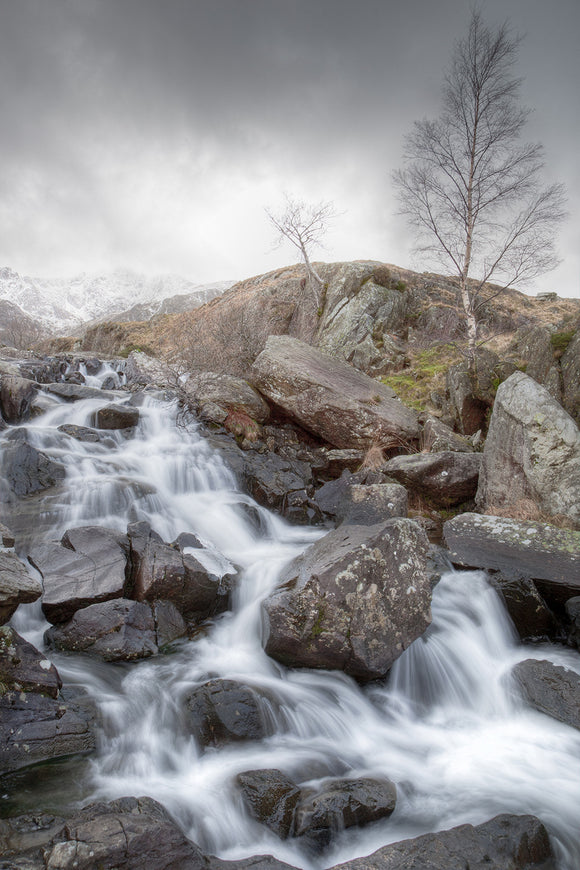 Rhaeadr Idwal is the waterfall on the path leading from Llyn Ogwen towards Cwm Idwal. A cold Winter's day with grey skies and snow covered mountains as the water cascades over the rocks