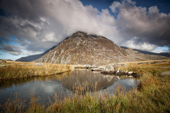 Pen yr Ole Wen, Snowdonia - stands beneath a blue, cloudy sky, reflecting in the waters of Llyn Idwal. A beautiful Welsh Countryside scene