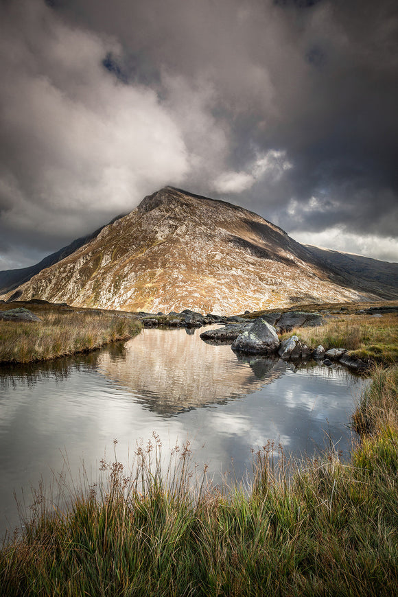 Pen yr Ole Wen, Snowdonia - An image taken from Cwm Idwal, looking towards Pen yr Ole Wen with stormy clouds above. An upright image of the mountain reflecting in the still waters of the lake. North Wales
