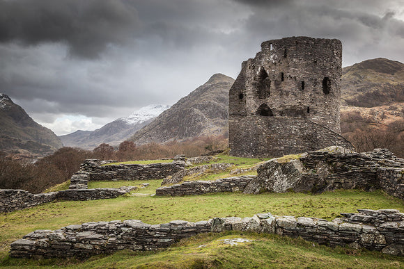 A Castle in the Mountains - Dolbadarn Castle stands below some stormy looking clouds on the hillside above llyn padarn in llanberis, Snowdonia National Park