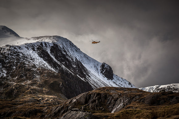 RAF Mountain rescue in Snowdonia. The now retired, yellow Seaking helicopter flies around the snow covered mountains surrounding llyn Idwal