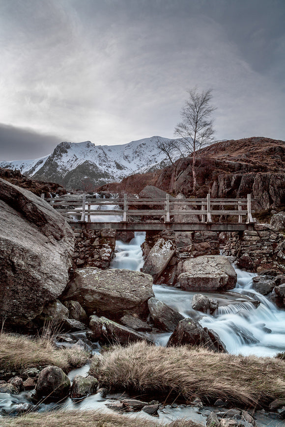Icy Waters at Rhaeadr Idwal, Snowdonia - North Wales. Water flows beneath the bridge that crosses this popular waterfall. Snow covered mountains in the background below grey clouds skies