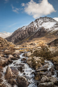 A photograph from below, looking upstream towards the imposing mountain of Tryfan. A lovely Winter's day with cloudy blue sky above the snow topped mountain. Ogwen Valley, Snowdonia, North Wales