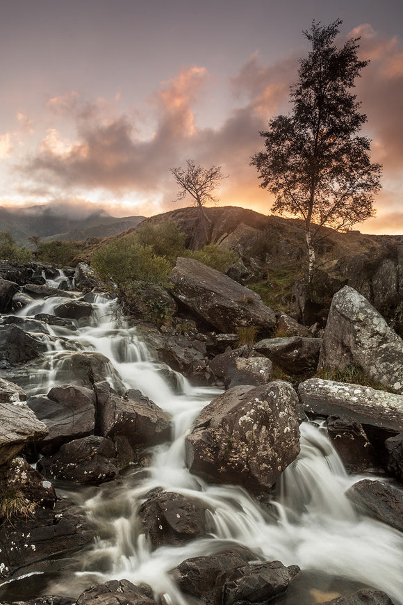 Rhaeadr Idwal, one of the most popular waterfalls in Snowdonia. Water cascades over the rocks as the orange colours of sunset fill the sky above. Snowdonia, North Wales