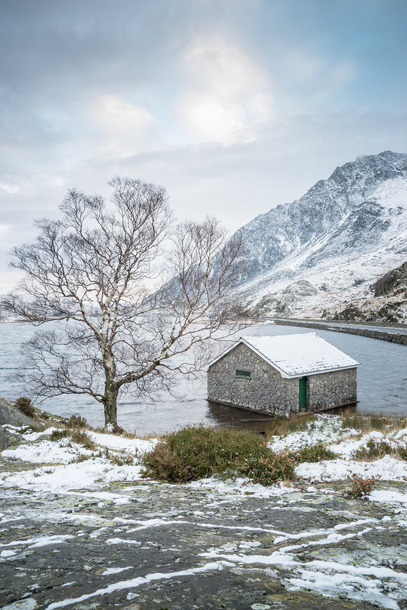A Winter's day at Llyn Ogwen. A more unusual upright landscape showing blue cloudy skies above llyn ogwen and a small amount of snow on the ground. Snowdonia National Park, North Wales