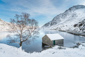 Snowfall at Llyn Ogwen - A crisp, Winter's day in Snowdonia National Park. White snow lays all around while the blue sky above reflects on the frozen surface of Llyn Ogwen