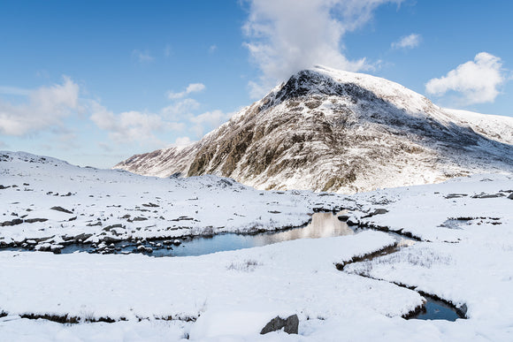 The Snowy Stream to Pen yr Ole Wen, Snowdonia - North Wales. A thick layer of snow lays on the ground at Cwm Idwal looking towards Pen yr Ole Wen with blue skies and cloud