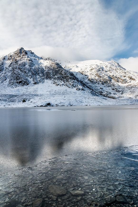 Llyn Idwal, Broken Reflections, Snowdonia - North Wales. A Winter scene at Llyn Idwal where the snow covered mountains are reflecting in the frozen surface of the lake below. The ice has broken around the edges of the lake