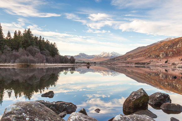 A Winter's day at Capel Curig looking along the lake of Llyn Mymbyr towards the snow covered mountains of the Snowdon Horseshoe. Beautiful reflections of the trees and hillside in the perfectly still water. North Wales