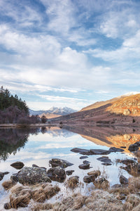 Llyn Mymbyr, Snowdonia - North Wales. An upright image with rocks in the foreground, looking across the still lake, reflecting it's surroundings, to Snowdon Horseshoe in the distance