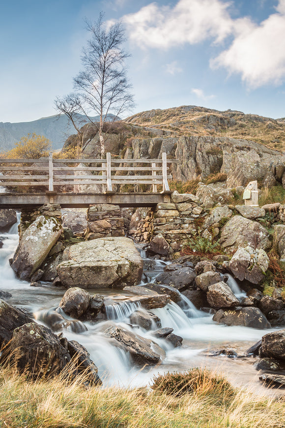 The Bridge across Rhaeadr Idwal, Snowdonia. Beautiful blue skies above this popular waterfall in Snowdonia, North Wales. Water flows over the rocks below the wooden bridge that spans the falls