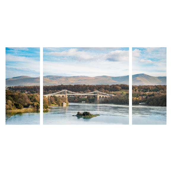 Canvas Wrap Triptych Wall Art - Blue Skies at Menai Bridge, Anglesey - North Wales. A Panoramic image of Menai Bridge with the blue sky reflecting into the water of the Menai Straits. Clouds sit in the sky above the hills behind the bridge and the trees surrounding are vibrant green colours. Image split into 3 panels to make a triptych image. Smart Imaging & Framing Landscape Photography