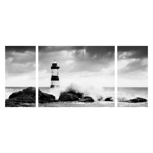 Canvas Wrap Triptych Wall Art - Crashing Waves at Penmon Lighthouse, Anglesey - North Wales. Dark, stormy clouds gather above as the waves of the incoming tide crash against the rocks in front of this iconic landmark of the Ynys Mon coastline. Black & White Panoramic image displayed as a triptych. Smart Imaging & Framing Landscape Photography
