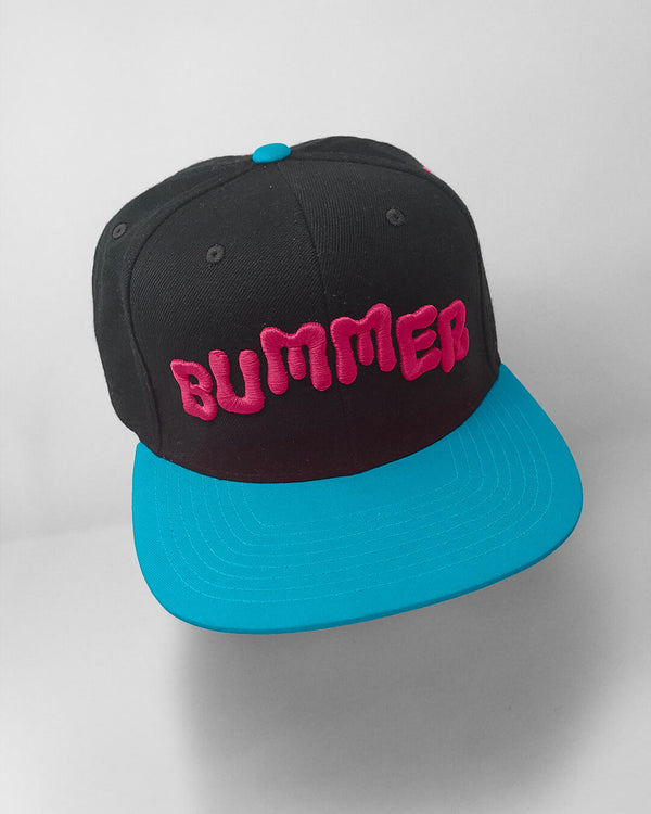 A black and light blue hat with bummer on it in pink embroidery..