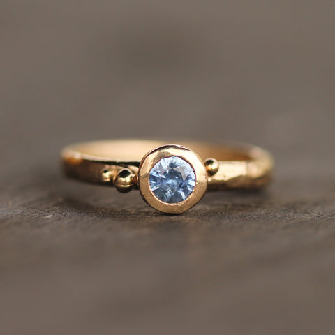 This ring balances classic solitaire design, with contemporary, playful charm. It has a subtly hand-carved texture that is reminiscent of a naturally smoothed beach pebble.   Made in 14k yellow gold with a cobalt blue sapphire.