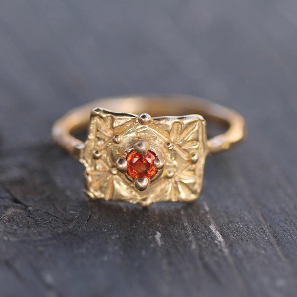 Orange sapphire surrounded by golden bubbles in a unique ring