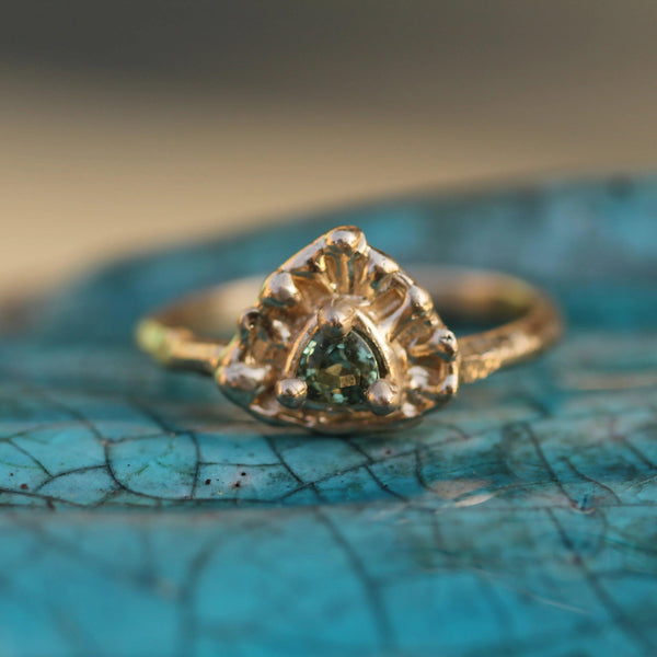 Golden bubbles surround a green sapphire in 14k yellow gold