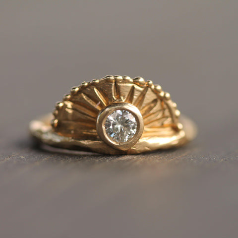 Hand carved ring inspired by a sunrise.  The centre stone is surrounded by rays of sunshine and golden bubbles.