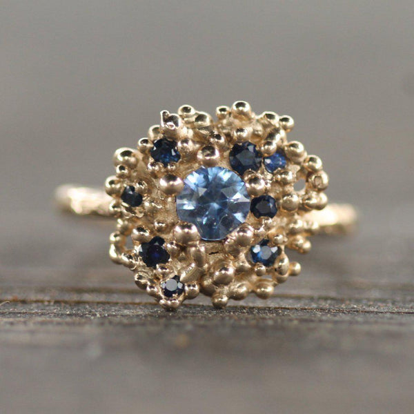 This ring features a cobalt blue centre stone and is surrounded by 14k gold bubbles and smaller dark blue sapphires