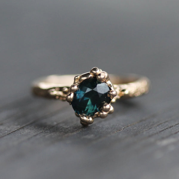 Deep teal sapphire ring surrounded by bubbles and made in 14k yellow gold.