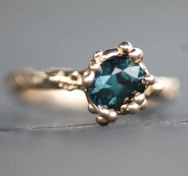 Close up picture of the teal sapphire.  In some light is appears to look green and others blue.