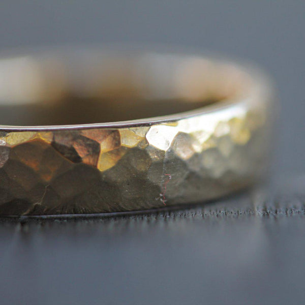 Hammered men's gold wedding band pictured close up