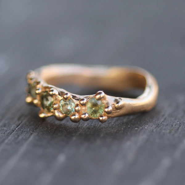 Light green sapphires featured in a gold band
