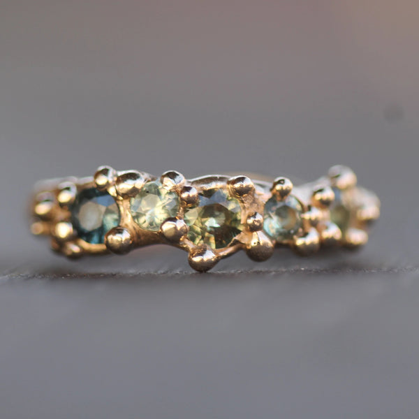 Unique gold sapphire ring with five varying colours of green and blue