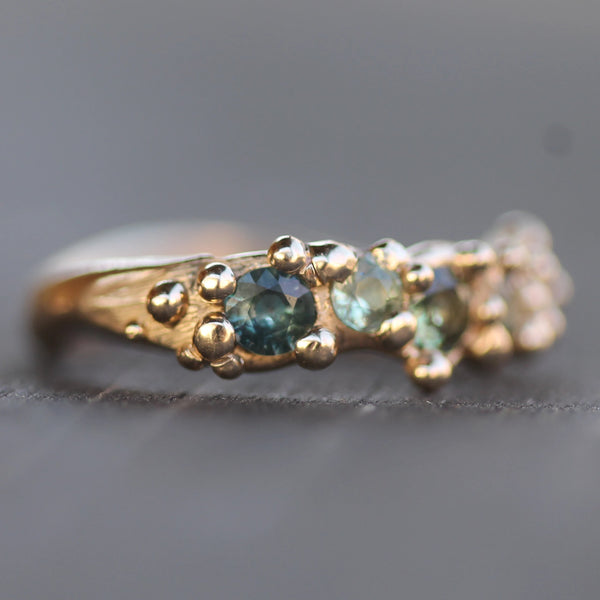 Close picture of the darker green blue sapphire and the golden bubbles