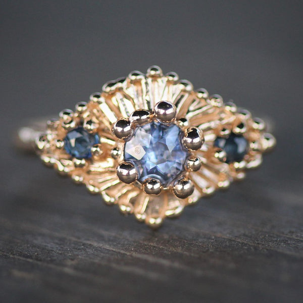 Cobalt blue sapphire surrounded by golden bubbles and a smaller sapphire either side