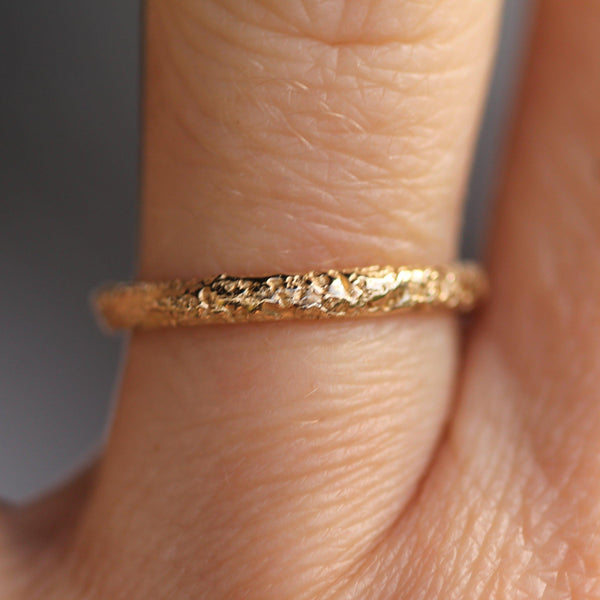 Sand textured gold wedding band pictured on a finger