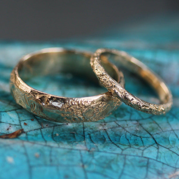 Two golden wedding bands pictured on blue turquoise